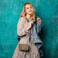 attractive stylish blonde woman in jeans oversize jacket walking against wall fashion