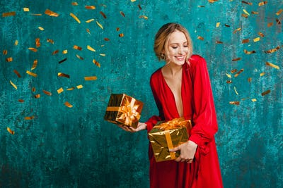 woman in red dress celebrating new year holding presents