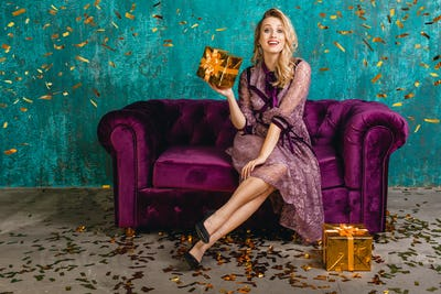 attractive smiling sexy woman in stylish violet lace evening luxury dress lying on velvet sofa