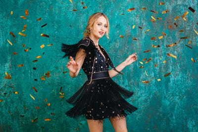 woman in party dress celebrating new year with golden confetti