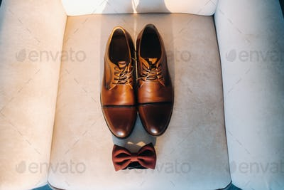 brown bow tie on a light background and boots