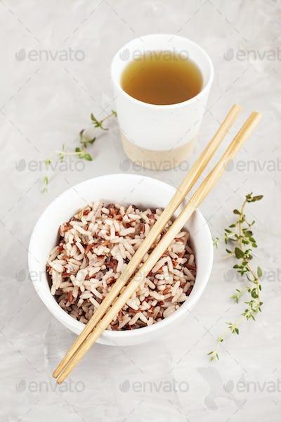 Assorted multi-colored wild rice in ceramic bowl and chopsticks