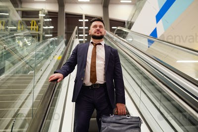 Businessman moving down escalator