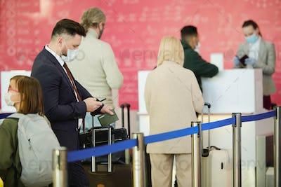 Travellers standing in queue