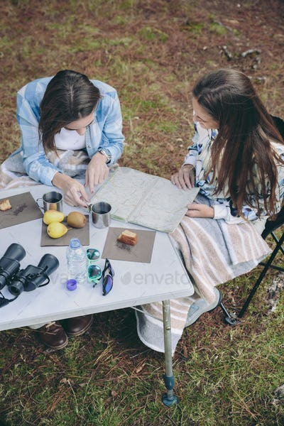 Young women looking road map in campsite