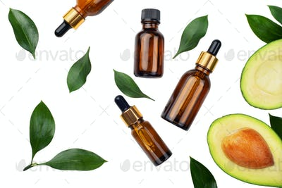 Dropper bottles with fresh ripe avocado and essential oil on white table flat lay