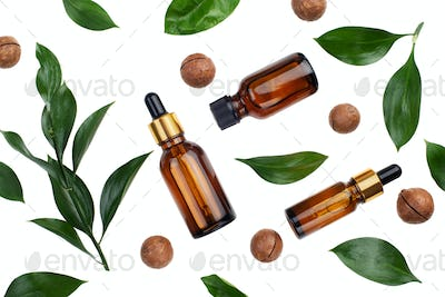 Dropper bottles with macadamia nut essential oil on white table flat lay
