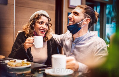 Happy couple with open mask having fun together at bar cafeteria