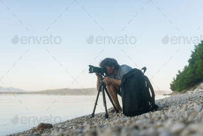 Male photographer taking photos on a pebble beach