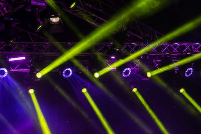 blue luminous rays from concert lighting against a dark background, musical instrument concept