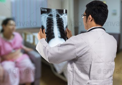 Back side of Doctor see x-ray film and diagnose on Abstract photo blurred of patient room