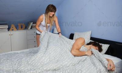 Woman waking up her husband