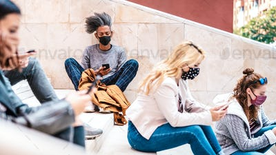 Urban millennial people using smart phones with face mask on Covid third wave