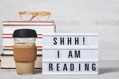 Pile of books, lightbox with the text, cup of coffee