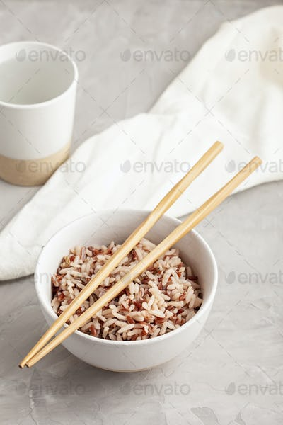 Assorted multi-colored wild rice in ceramic bowl and chopsticks with goblet of water