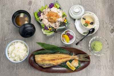 Top view of japanese foods set, fried fish serve with stream rice and pork yum salad with egg stream