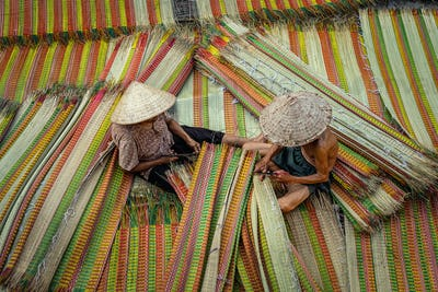 Top view of old Vietnamese lover craftsman making the traditional vietnam mats