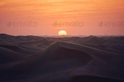Sand dunes in desert landscape at beautiful sunset