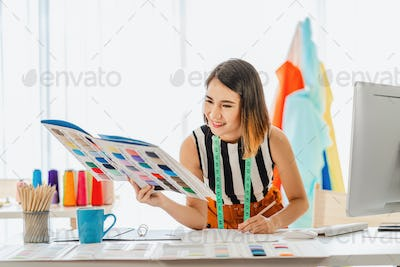 Young Asian designer woman choosing multicolor chart and writing noted at workplace