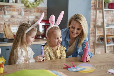 Mother and two little daughters playing with handmade Easter toys
