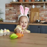 Playful girl in rabbit ears taking a carrot from the table