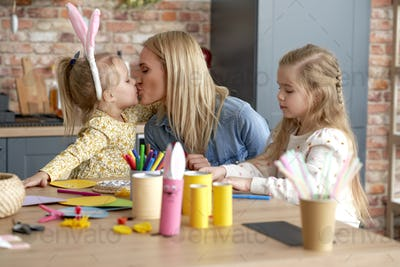Cute kissing mom with daughters during preparing Easter decorations