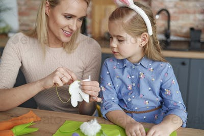 Mother teaches her little daughter sewing Easter decorations