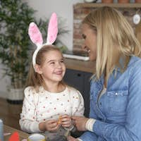 Happy mom and daughter preparing Easter decorations together