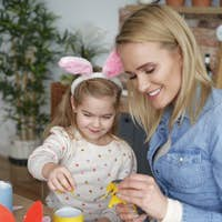 Happy mom and daughter preparing Easter decorations together at home