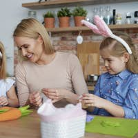Happy mother and daughters preparing Easter decorations at home