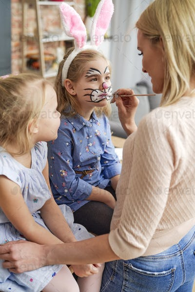 Mom painting an Easter bunny on her daughter's face