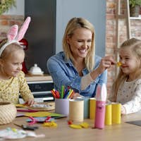 Mother and two little daughters have fun making Easter decorations