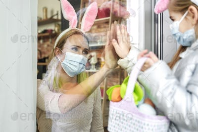 Mother greeting little daughter during the Easter quarantine
