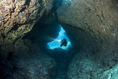 Scuba Diver with LIght Enters Coral Cavern