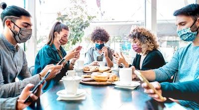 Millenial people using mobile smart phones at coffee bar