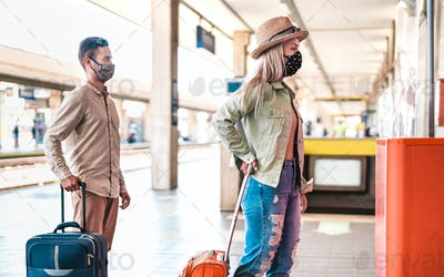 Young couple waiting in line practising social distancing at train station