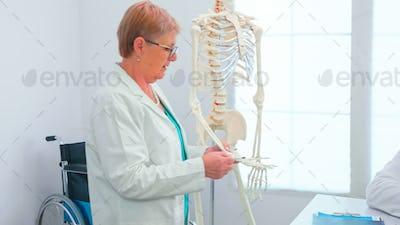 Medical doctor woman teaching anatomy using human skeleton