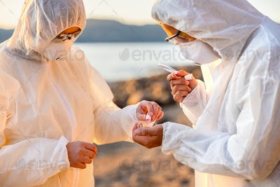 Young multi-ethnic scientists discussing water samples at beach