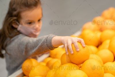 Hand of cute little girl in casualwear and protective mask taking fresh orange