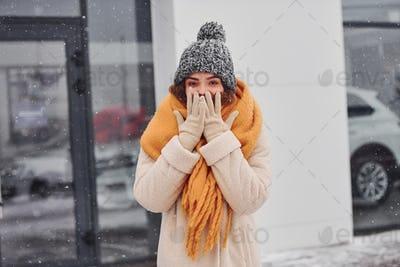 Cheerful young girl smiling standing and smiling outdoors. Snow is falling