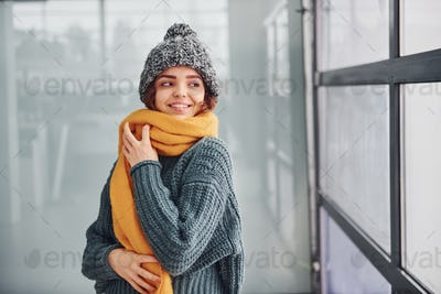 Beautiful cheerful girl in yellow scarf and in warm clothes standing indoors