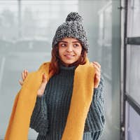 Beautiful cheerful girl in yellow scarf and in warm clothes standing indoors against background