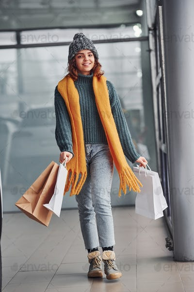 Beautiful cheerful girl in yellow scarf and in warm clothes standing indoors with shopping bags