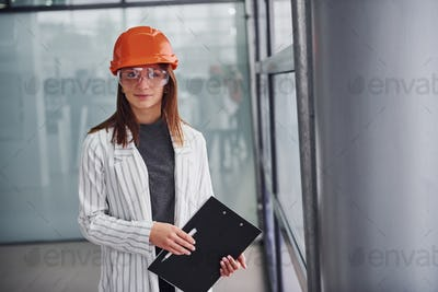 Portrait of young female worker with protective helmet, eyewear and notepad. Standing in the office