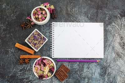 notebook and pen with dry flowers and chocolate on grey background