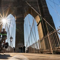 Scene of stop motion bicycle with Brooklyn bridge when sunrise, USA downtown skyline,
