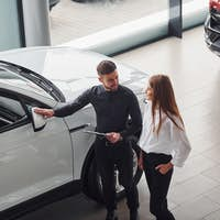 Woman choosing car by help of male assistant indoors in the salon