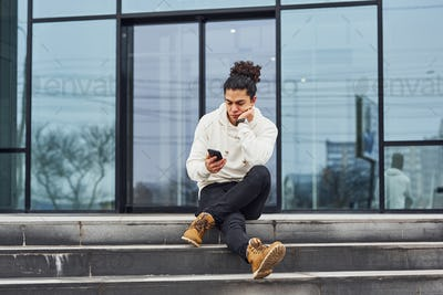 Handsome young man with curly black hair and with smartphone in hands is on the street