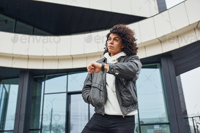 Handsome young man with curly black hair posing for the camera on the street against building