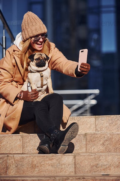 Woman in warm clothes make selfie with her little pug dog near business building that on background